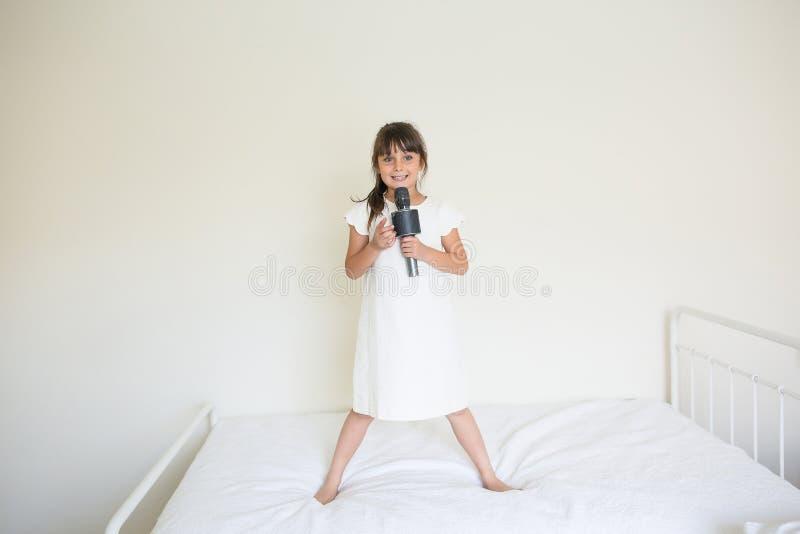 Flicka med en mikrofon på säng royaltyfria foton