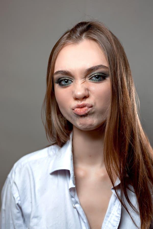 Flicka med en missnöjd framsida i en skjorta royaltyfria foton