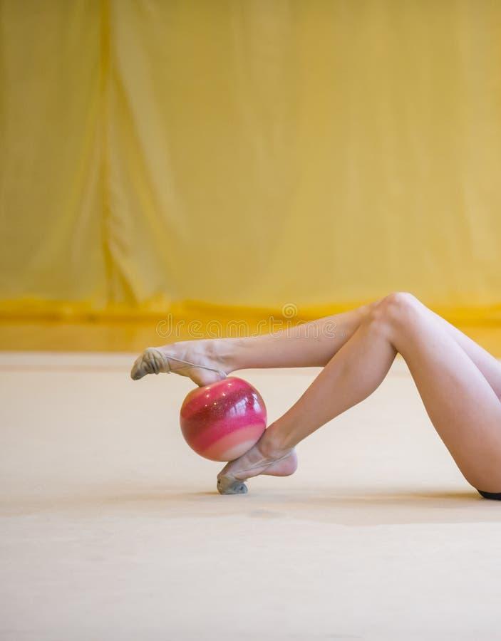 Flicka med en röd boll för rytmisk gymnastik Böjlighet i akrobat royaltyfri bild