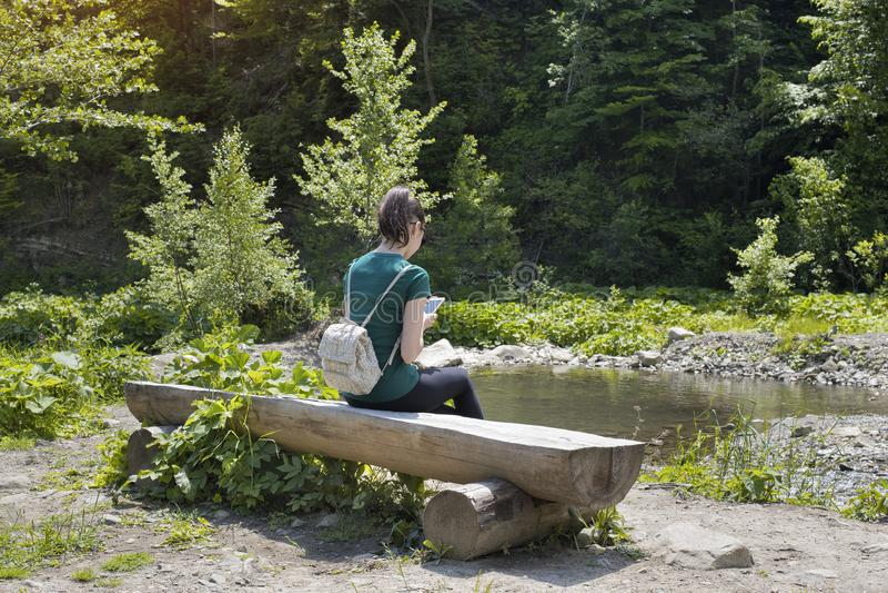 Flicka med en ryggsäck och ett smartphonesammanträde på en flodbank S royaltyfri foto