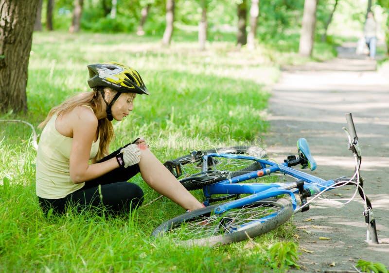 Flicka med en skada från en nedgång från en cykel arkivbilder