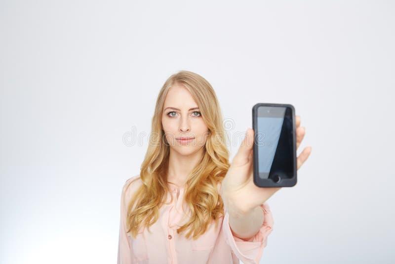 Flicka med en smart telefon Isolerat på vit royaltyfria foton