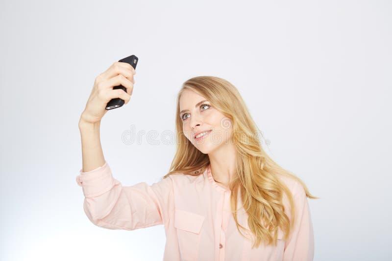 Flicka med en smart telefon Isolerat på vit fotografering för bildbyråer
