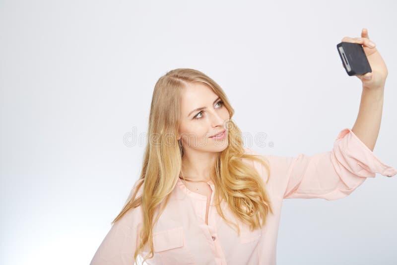 Flicka med en smart telefon Isolerat på vit royaltyfri bild
