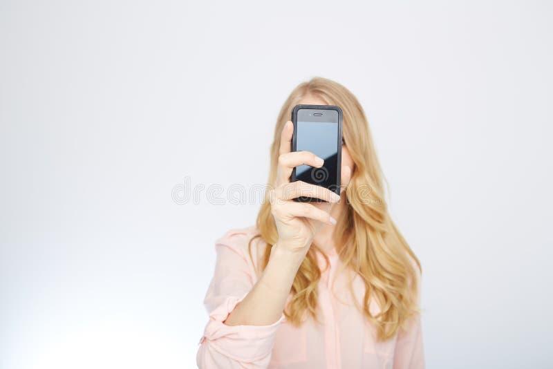Flicka med en smart telefon Isolerat på vit arkivfoton