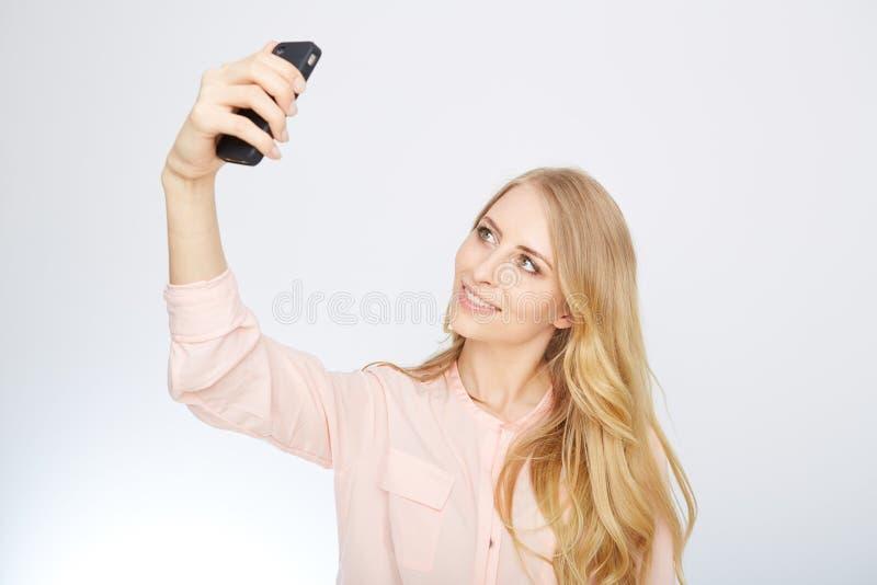 Flicka med en smart telefon Isolerat på vit arkivbilder