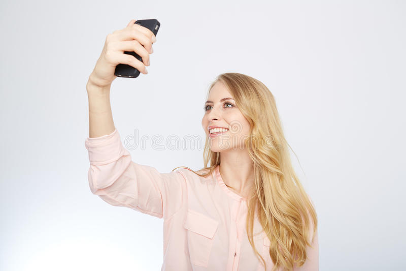 Flicka med en smart telefon Isolerat på vit royaltyfri fotografi