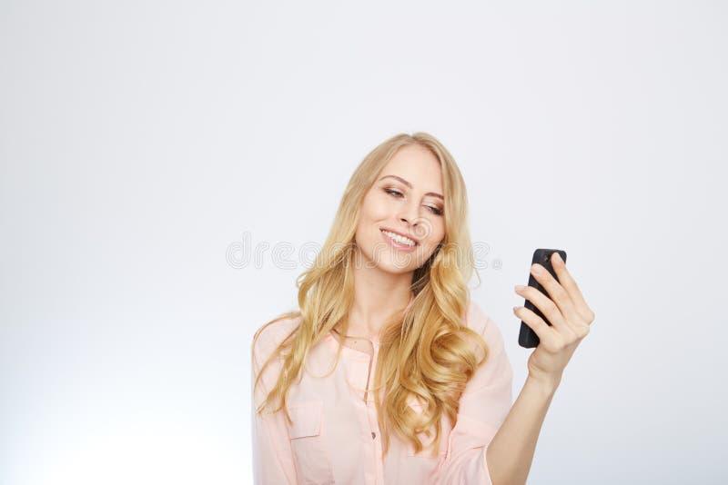 Flicka med en smart telefon Isolerat på vit arkivbild
