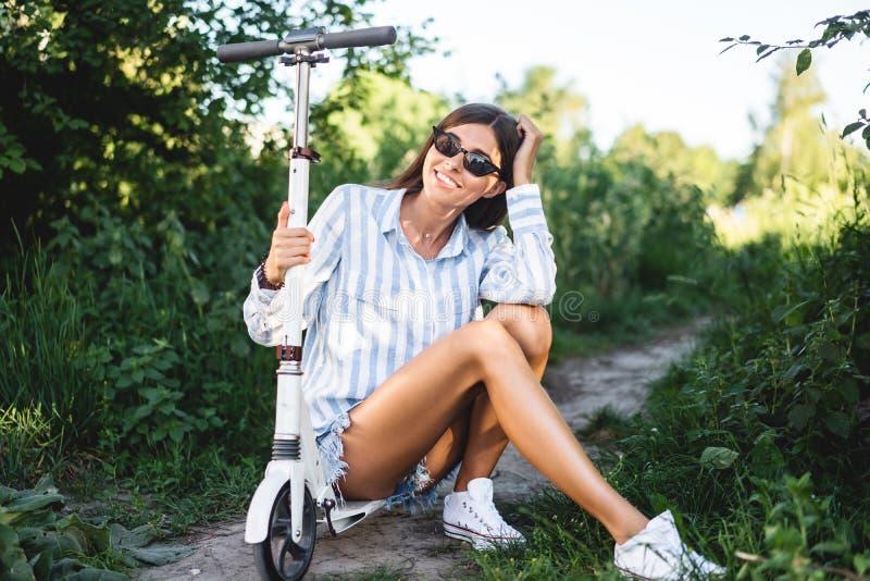 Flicka med en sparkcykel i naturen som poserar på kameran royaltyfria bilder