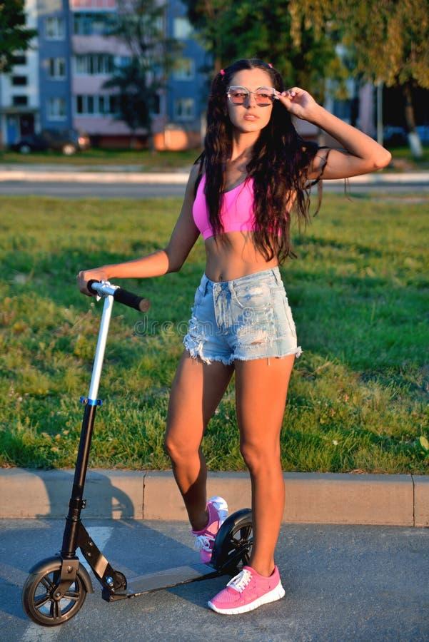 Flicka med en sparkcykel i en rosa överkant och blåa kortslutningar, solglasögon, e arkivfoton