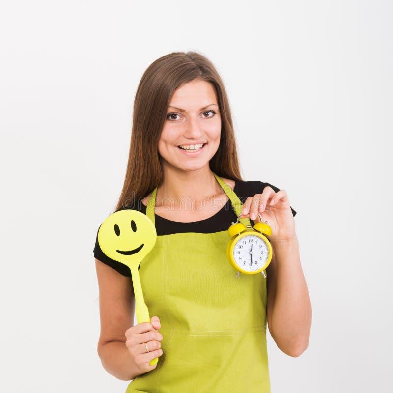 Flicka med en spatel och en klocka arkivbild