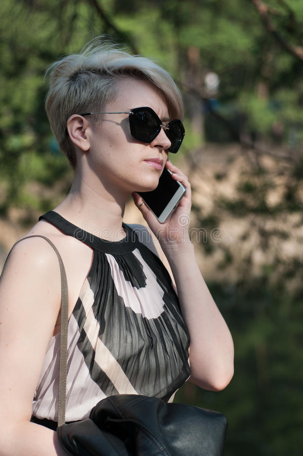 Flicka med en telefon i henne händer arkivfoto