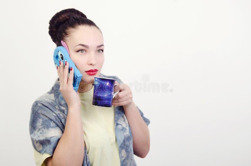 Flicka med en telefon och en kopp arkivfoto