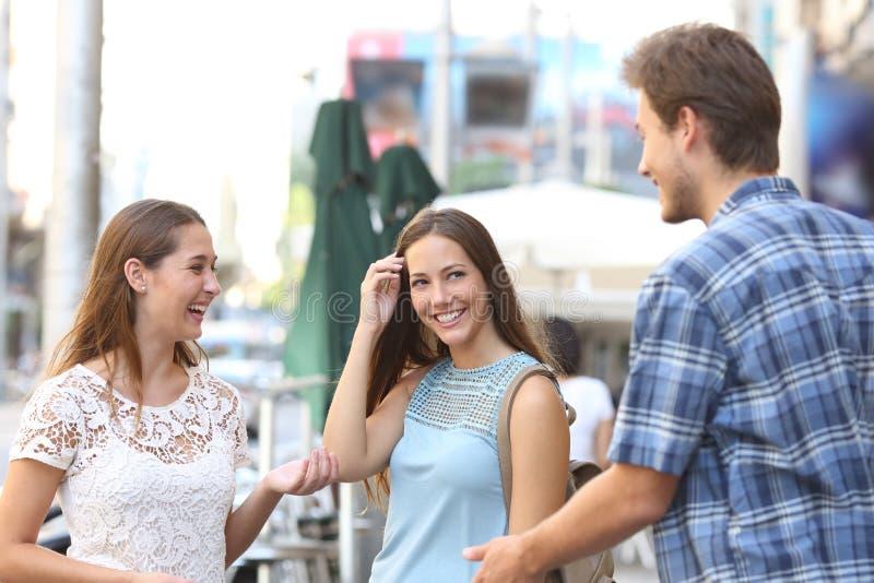 Flicka med en vän som flörtar med en pojke fotografering för bildbyråer