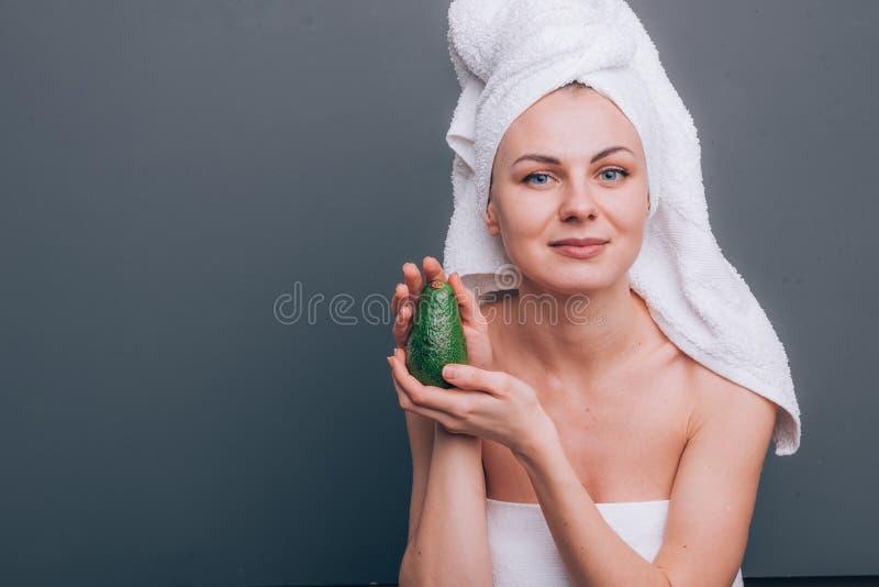 Flicka med en vit handduk på hennes huvud med en näringsrik grön maskering på hennes framsida och en avokado i hennes händer på e royaltyfri fotografi