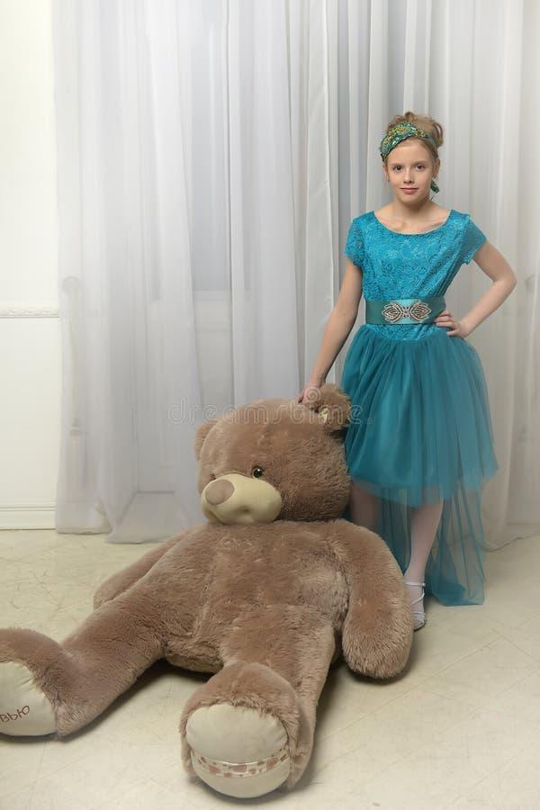 Flicka med enormt teddybear arkivbild