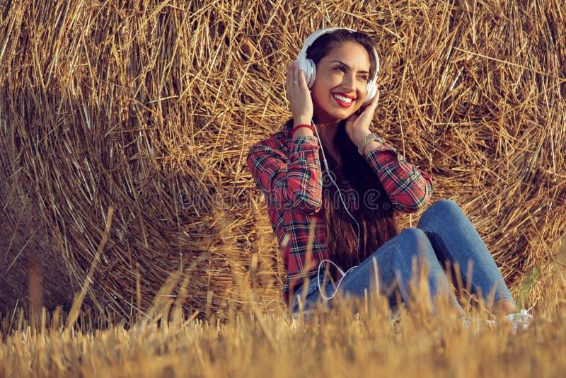 Flicka med ett härligt leende som tycker om musik arkivbild