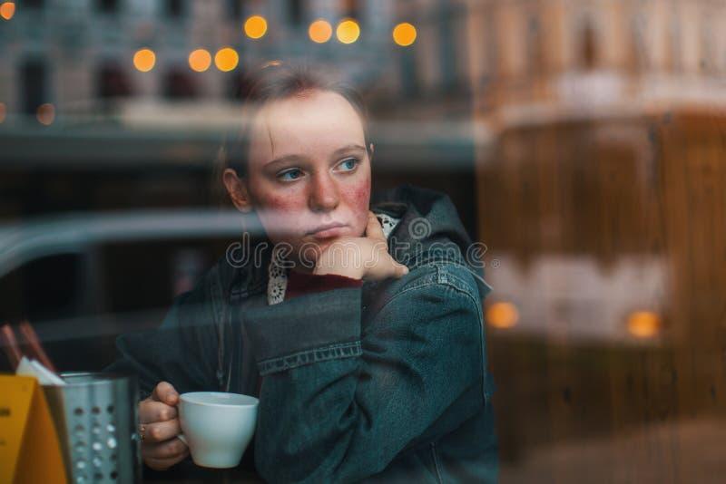 Flicka med ett kopp kaffesammanträde i ett kafé arkivbilder