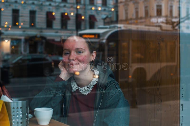 Flicka med ett kopp kaffesammanträde i ett kafé royaltyfri foto