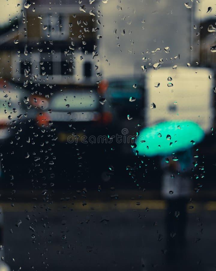 Flicka med ett paraply i bakgrunds- och vattendropparna i fokus royaltyfria foton