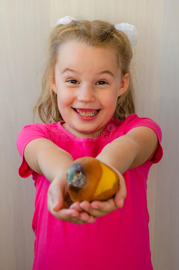 Flicka med ett ruttet päronbegrepp av bortskämd mat och att äta det arkivfoto