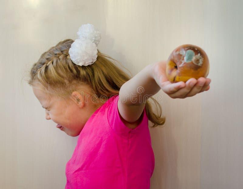 Flicka med ett ruttet päronbegrepp av bortskämd mat och att äta det royaltyfri fotografi