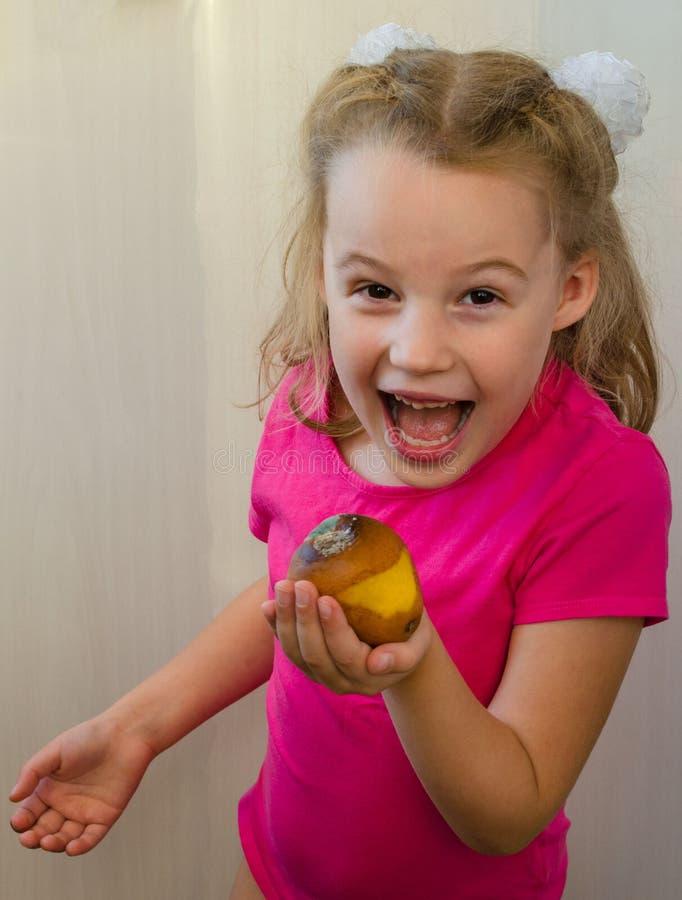 Flicka med ett ruttet päronbegrepp av bortskämd mat och att äta det royaltyfri foto