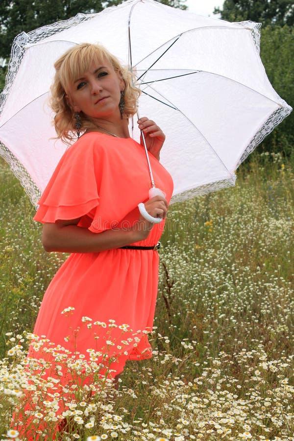 Flicka med ett vitt paraply, en lång klänning, ett fält av blommor, en rosa klänning härlig blond flicka i ett fält av blommor arkivfoto