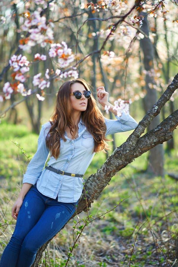 Flicka med exponeringsglas i träden royaltyfria bilder
