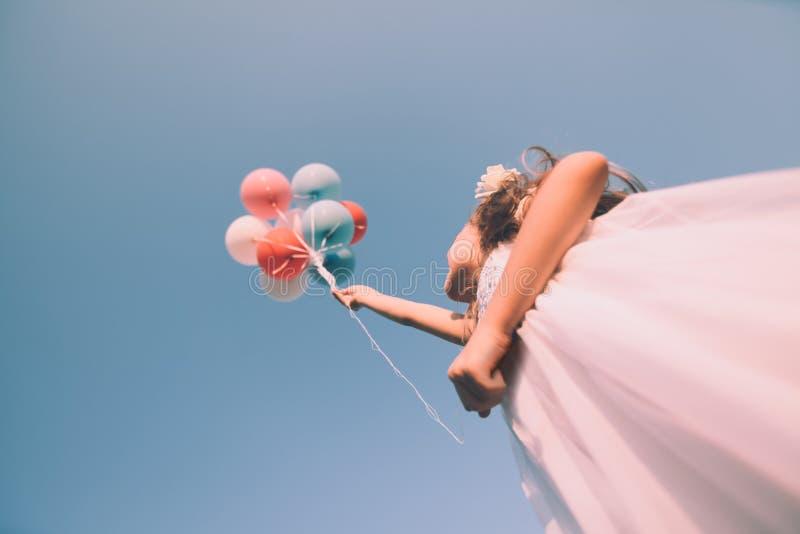 Flicka med färgrika ballonger upp i himlen Låg vinkel se retro arkivfoto
