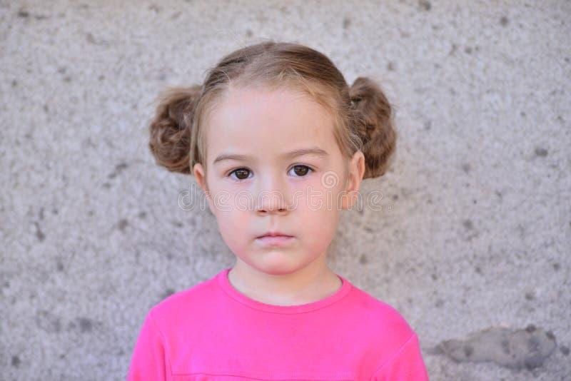 Flicka med flätade trådar mot väggen royaltyfria bilder