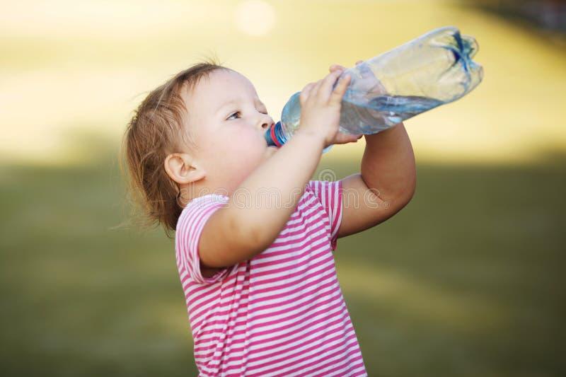 Flicka med flaskan av mineralvatten arkivfoto
