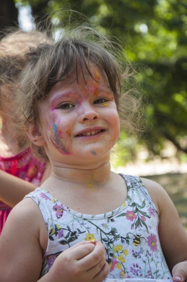 Flicka med framsidamålarfärg arkivfoto