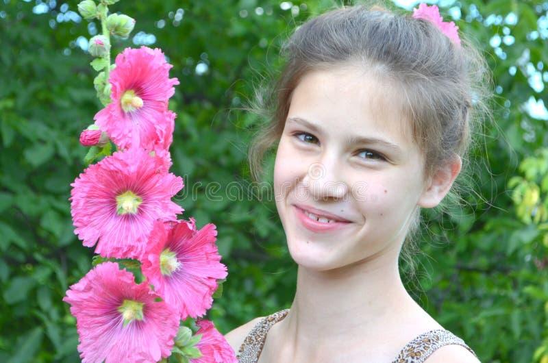 Flicka med frisyr- och rosa färgstockrors royaltyfria foton