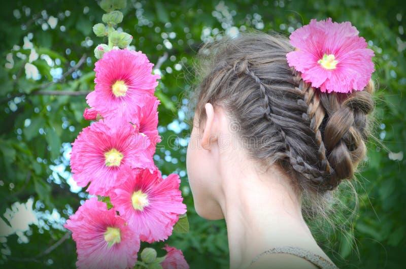 Flicka med frisyr- och rosa färgstockrors royaltyfria bilder