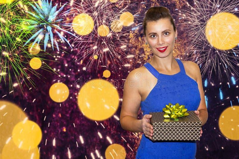 Flicka med gåvaasken på färgrik festlig bakgrund Den attraktiva unga kvinnan rymmer gåvaasken i händer arkivbild