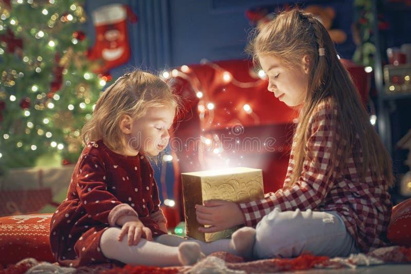 Flicka med gåvan nära julgranen arkivbild