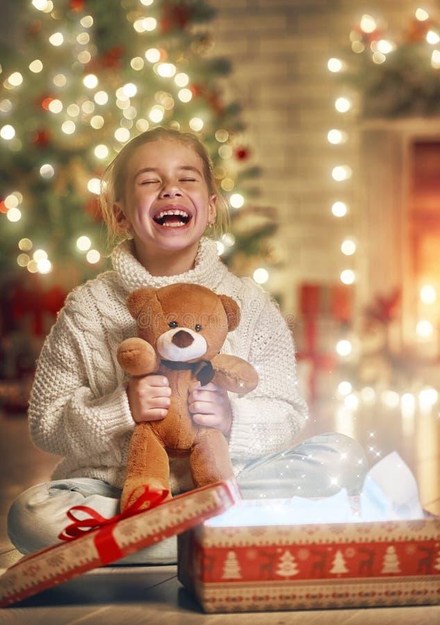 Flicka med gåvan nära julgranen fotografering för bildbyråer