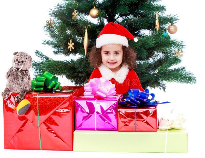 Flicka med gåvor nära julgranen royaltyfri bild