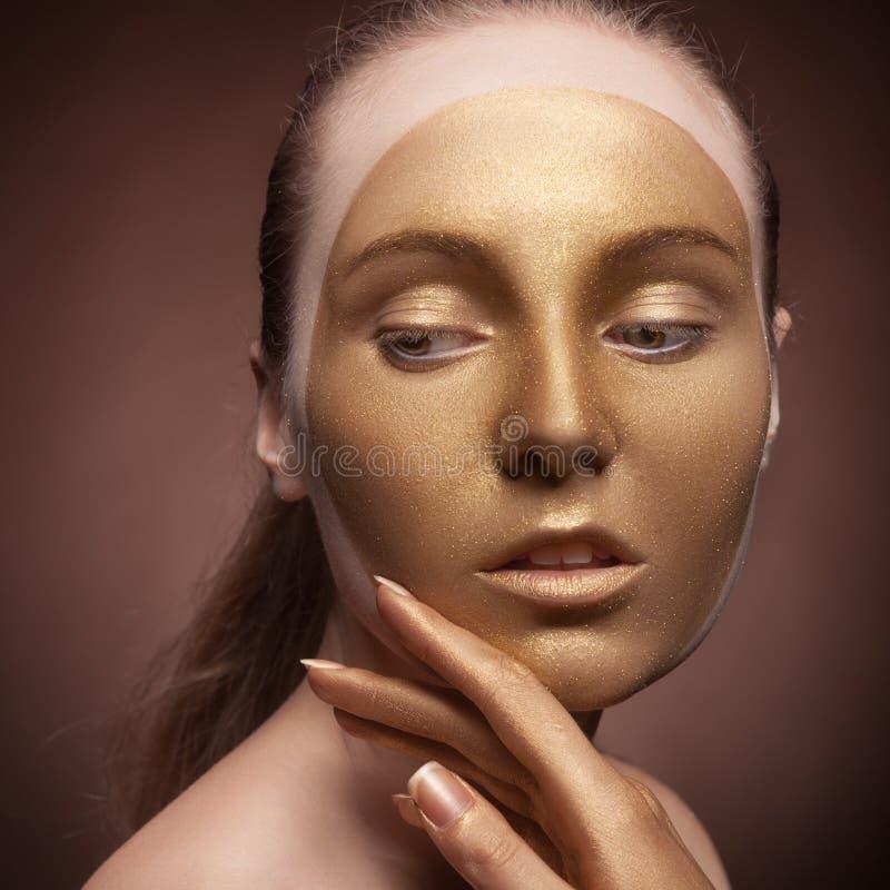 Flicka med guld- modesmink arkivfoto