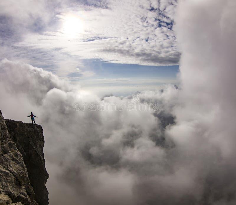 Flicka med händer upp anseende på en klippa i moln royaltyfria foton