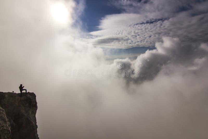 Flicka med händer upp anseende på en klippa i moln arkivfoto