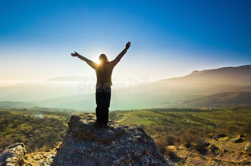 Flicka med händer upp i bergen mot solen royaltyfri foto