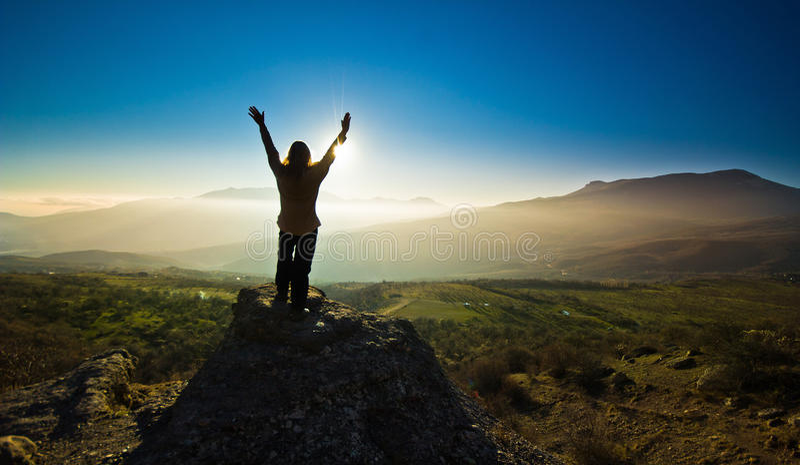 Flicka med händer upp i mountsinsna mot solen arkivfoton