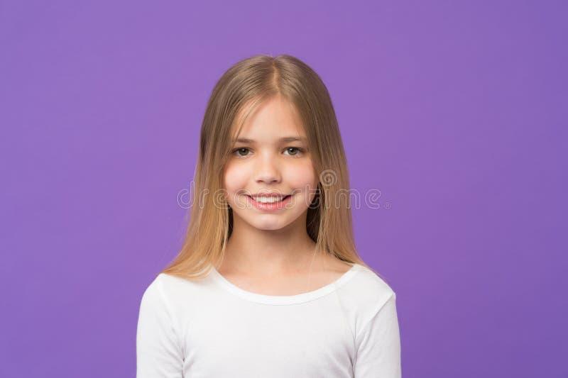 Flicka med härligt leende som isoleras på purpurfärgad bakgrund Barn med den gulliga framsidastudioståenden Modell med att skina  arkivfoton