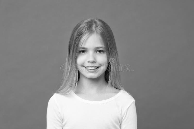 Flicka med härligt leende som isoleras på purpurfärgad bakgrund Barn med den gulliga framsidastudioståenden Modell med att skina  royaltyfri bild