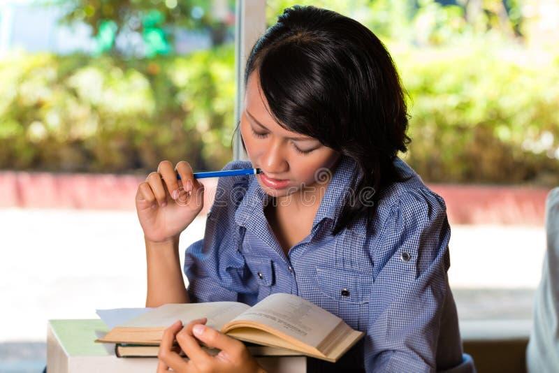 Flicka med högen av att lära för böcker royaltyfri foto