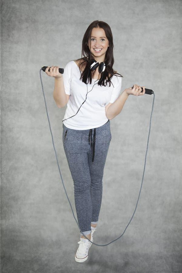 Flicka med hörlurar och repet royaltyfri fotografi