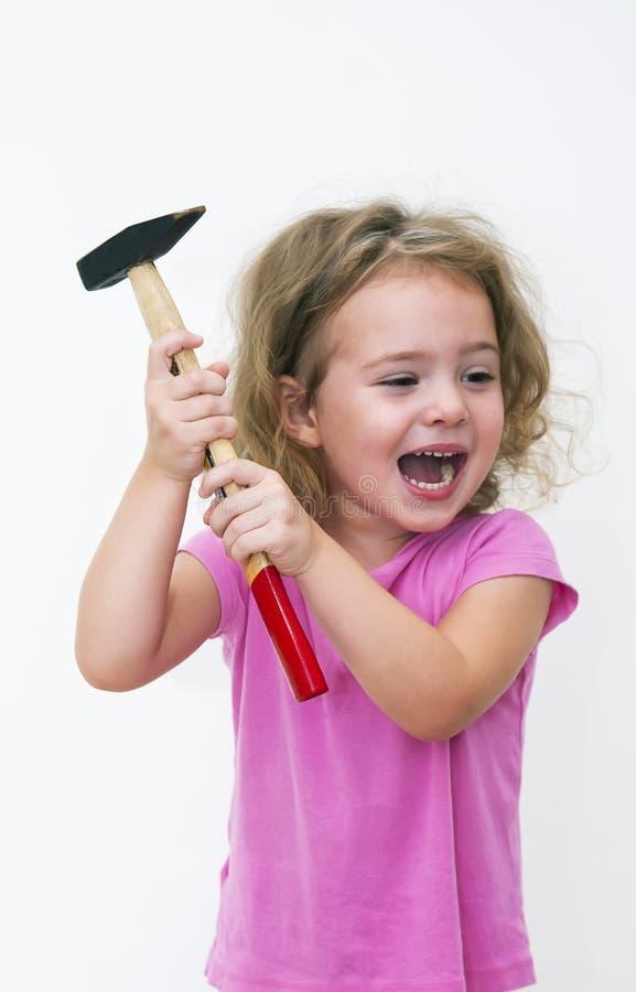 Flicka med hammaren och leende royaltyfri fotografi
