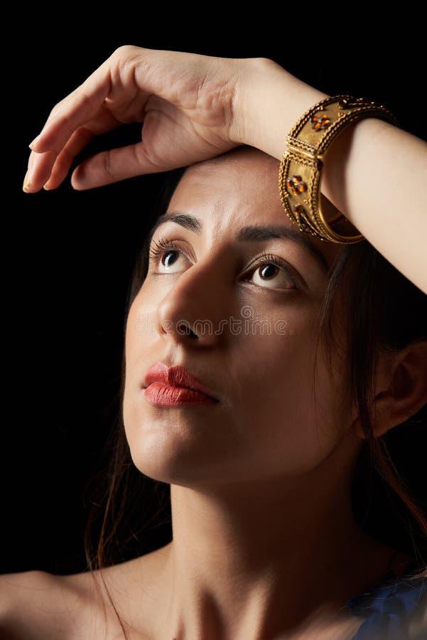 Flicka med handen på huvudet arkivbild